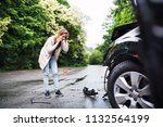 young woman by the damaged car... | Shutterstock . vector #1132564199