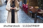 woman using phone in the street | Shutterstock . vector #1132659809