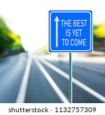 Small photo of The best is yet to come motivational phrase on blue road sign with arrow and blurred speedy background. Copy space.