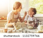 Small photo of Cute Little Girl and Her Beautiful Mom in Aprons Playing. Happy daughter with Her Mother Laughing While Kneading the Dough in Modern Kitchen at Sweet Home. Smiling Family Cooking Tasty Biscuit.