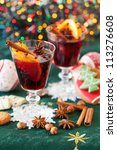 Two glasses of mulled wine, cookies and variation of Christmas spices - stock photo
