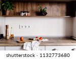 Stock photo wooden board with knife olive oil tomatoes towel on modern kitchen countertop and shelf with 1132773680