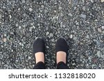 feet on ground of small stones... | Shutterstock . vector #1132818020