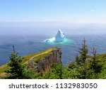 Incredible iceberg floating along the rugged coast beside the Skerwink Trail in Newfoundland and Labrador, Canada