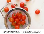tiny cherry tomatoes in a sieve.   Shutterstock . vector #1132983620