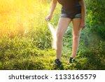 woman applying insect repellent ... | Shutterstock . vector #1133165579