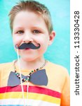 Cute boy with mustache and bow tie party accessories - stock photo