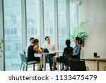 a diverse team sit around a... | Shutterstock . vector #1133475479