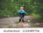 Happy Child Jumping In Puddle...