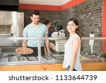 smiling woman choosing pizza at ... | Shutterstock . vector #1133644739