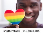 smiling man holding rainbow... | Shutterstock . vector #1134031586
