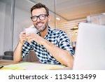 handsome designer drinking... | Shutterstock . vector #1134313499