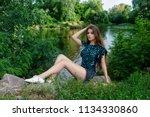 beautiful girl in denim shorts... | Shutterstock . vector #1134330860