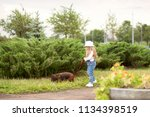 Stock photo lovely little blonde girl with long hair and in a hat walking with a dog in the park 1134398519