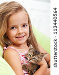 Little girl holding her kitten - shallow depth of field, closeup - stock photo