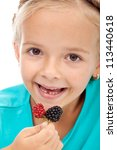 Little girl eating blackberries - closeup - stock photo