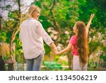 mother holding a hand of her... | Shutterstock . vector #1134506219