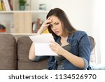 concerned woman reading bad... | Shutterstock . vector #1134526970