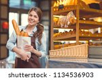 smiling baker with baguettes in ... | Shutterstock . vector #1134536903
