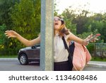 Small photo of Portrait of young inattentive girl, distracted by mobile phone. Girl crashed into street post, dropped phone