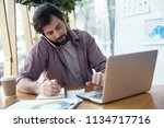 man sitting at the table at... | Shutterstock . vector #1134717716
