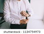 man fastens his cufflinks close ... | Shutterstock . vector #1134754973