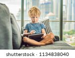 boy uses a tablet at home on... | Shutterstock . vector #1134838040