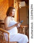 pregnant woman reads e-book in home interior - stock photo