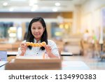 asian women eat donuts at the...   Shutterstock . vector #1134990383
