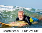 mature surfer ready to catch a... | Shutterstock . vector #1134991139