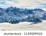 summits of the alps rising from ... | Shutterstock . vector #1135009010