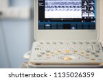 Small photo of Gray and orange button of the keyboard of the device for ultrasound examination against the background of the defocused screen with the image of the measurement of the ejection fraction.