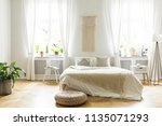 pouf next to bed with blanket... | Shutterstock . vector #1135071293