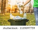 man hand putting plastic reuse... | Shutterstock . vector #1135097759
