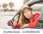 female driver showing middle... | Shutterstock . vector #1135306520