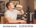 man drinking whey protein at... | Shutterstock . vector #1135313936