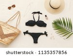 Black bikini swimsuit, straw boater hat, wicker beach bag, sunglasses, gold necklace, rings, tropical palm leave on beige background. Woman