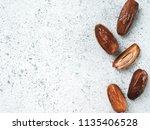 dried dates on gray cement... | Shutterstock . vector #1135406528
