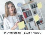 a young girl stands near a... | Shutterstock . vector #1135475090