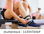 woman at gym putting ankle... | Shutterstock . vector #1135476569