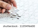 pieces of jigsaw on palm pieces ... | Shutterstock . vector #1135496600