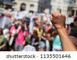 a raised fist of a protestor at ... | Shutterstock . vector #1135501646