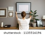 girl hanging a frame on a gray... | Shutterstock . vector #1135516196