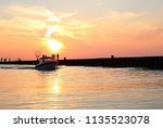 Small photo of Gorgeous sunset at station beach over Lake Huron in Kincardine, Ontario with a small fishing boat coming in to the harbor