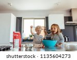 young girl licking batter from... | Shutterstock . vector #1135604273