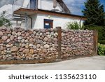 a house with a fence made of... | Shutterstock . vector #1135623110