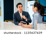Small photo of An Asian Chinese man in a suit has a discussion with his Eurasian woman colleague in an office during the day. They are both holding mugs of a hot beverage (coffee or tea) and talking.