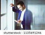 business man in suit talking on ... | Shutterstock . vector #1135691246