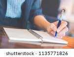 business woman hand writing on... | Shutterstock . vector #1135771826