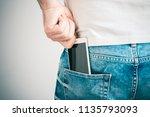 male hand grabbing a smartphone ... | Shutterstock . vector #1135793093